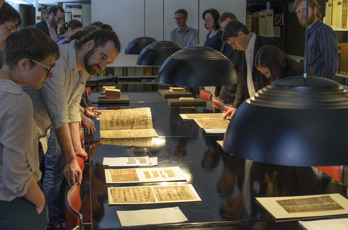 Fragmentologists walking around a table, admiring the HAB Wolfenbüttel's collection of loose fragments.